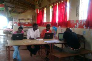 Computer Lab Teacher Issac works with his students