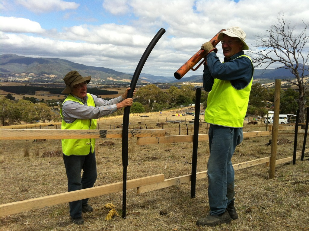 Volunteers securing steel droppers on the fence