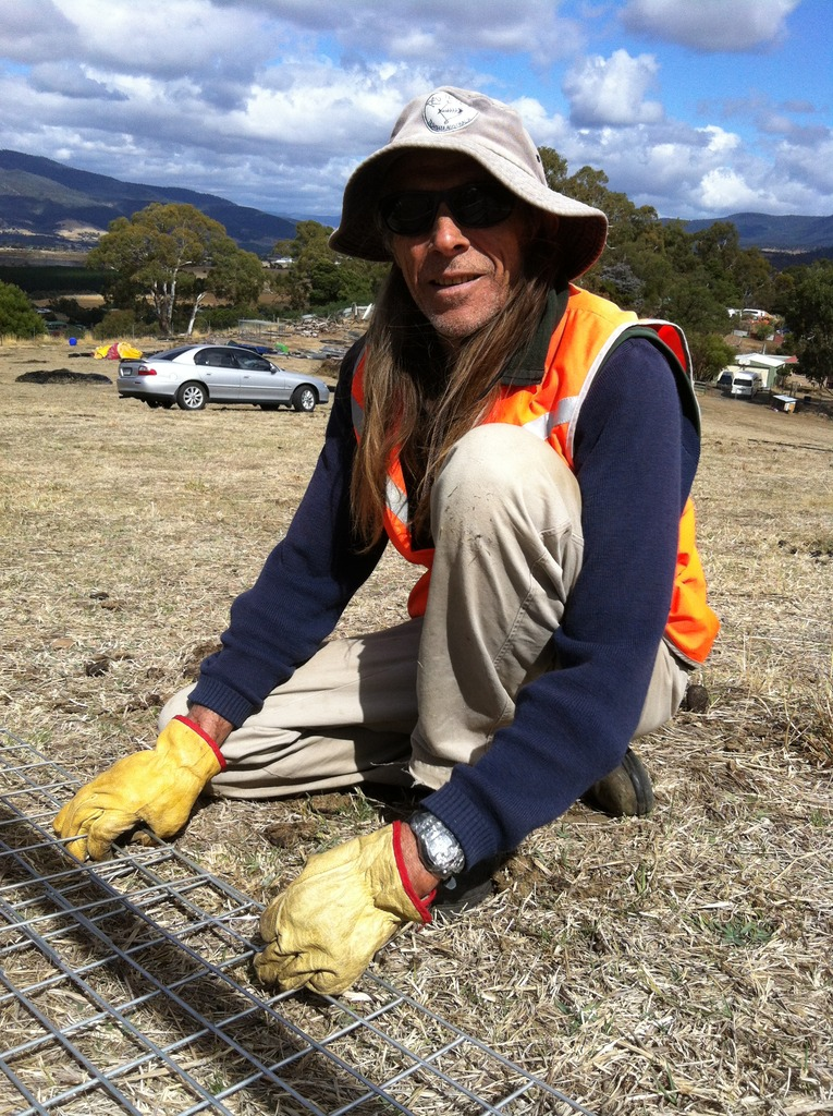 Volunteer installing wire mesh to prevent escapees