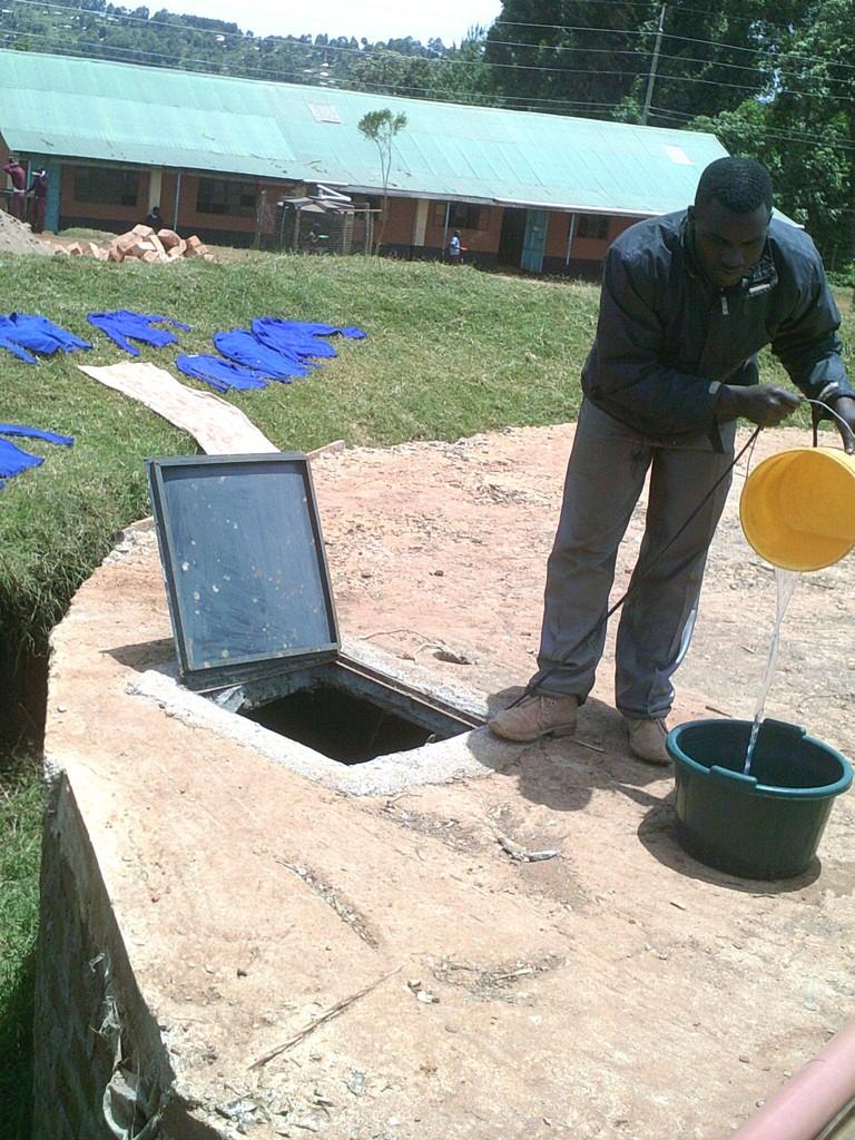 Staff member retrieves water from tank