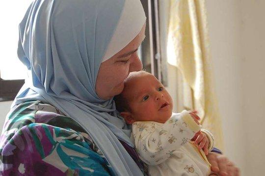 UNHCR's field worker holds a newborn UNHCR/Purvis