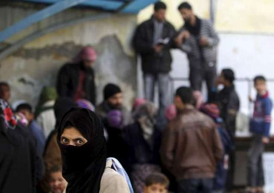 Displaced Syrians wait for aid. Reuters