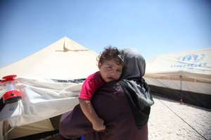 A Syrian mother holds her child in a refugee camp