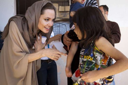 Angelina Jolie visits with a young Syrian refugee.