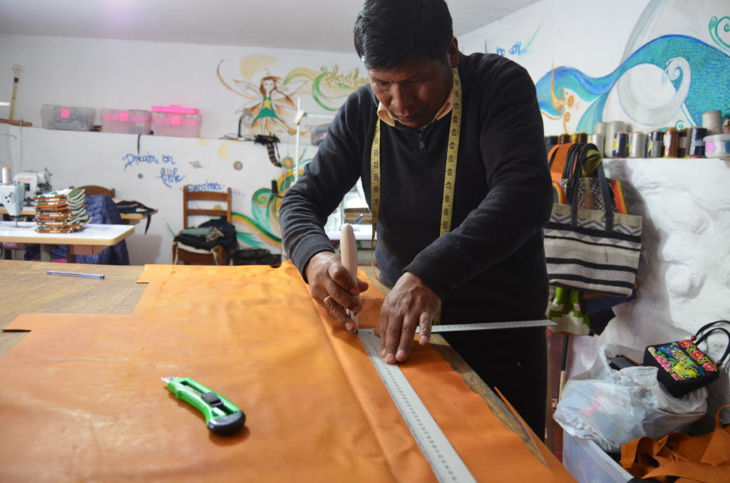 Senor Tomas cutting leather