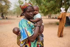 A Malian mother carries children in Burkina Faso