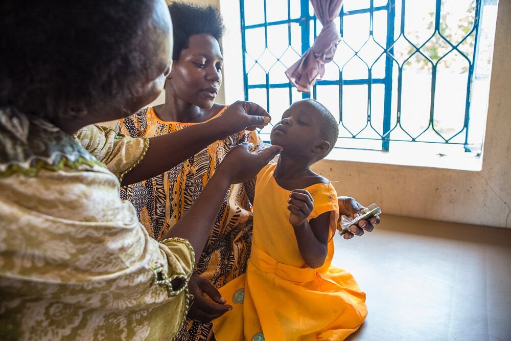 Child taking drops at clinic