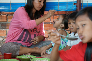 Housemother feeding Riverkids' Daycare toddlers
