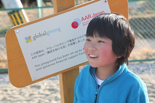 A boy from Temporary Housing Complex at signboard