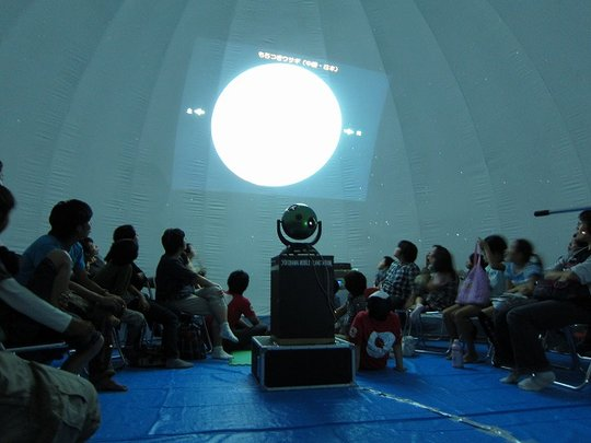 Children eagerly look up at the planetarium.