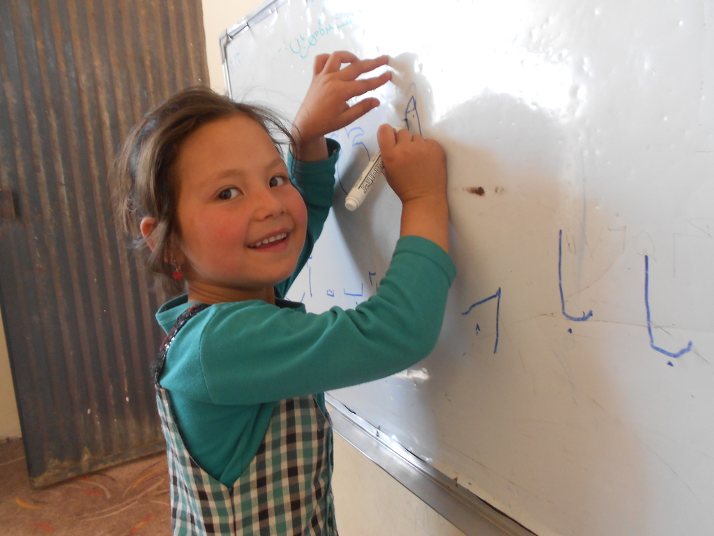 Homaira practices writing at the daycare center.