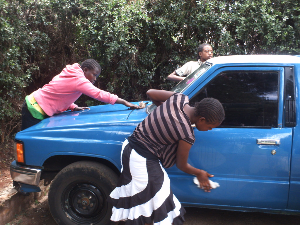 Girls learning to wash cars