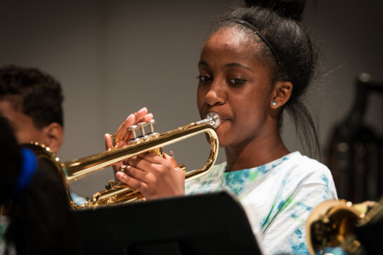 A trumpeter plays with dedication!