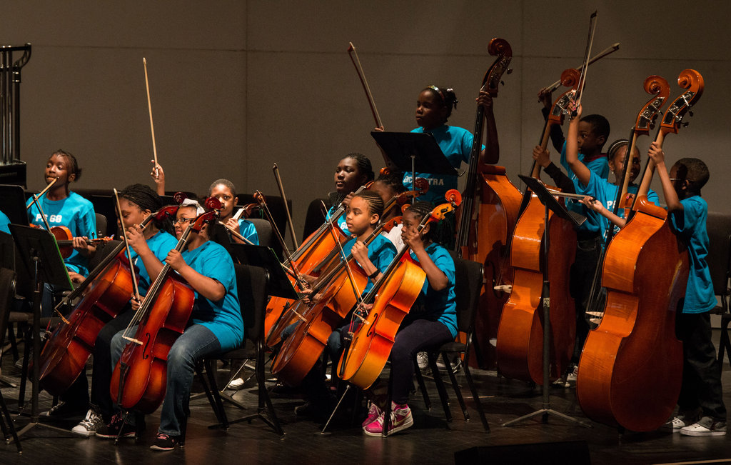 An orchestra prepares to play their song.