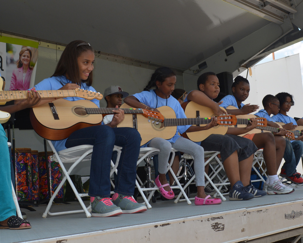 Strumming onstage at a community performance
