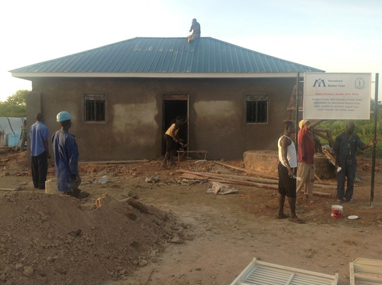 A construction crew rebuilds the clinic roof.