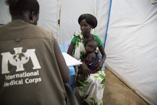 A clinical health worker helps a mother and child