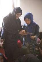 AIL student reading with Dr. Sakena Yacoobi
