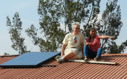 Fatima and volunteer hang out by their 245W panel