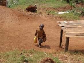 Small boy collecting water in Bushekeri