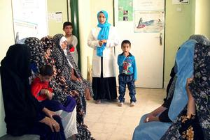 A health educator speaking with mothers