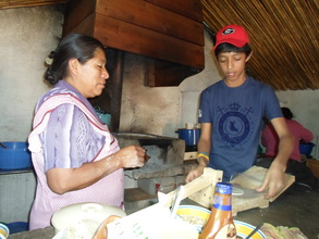 A boy learning how to make tortillas