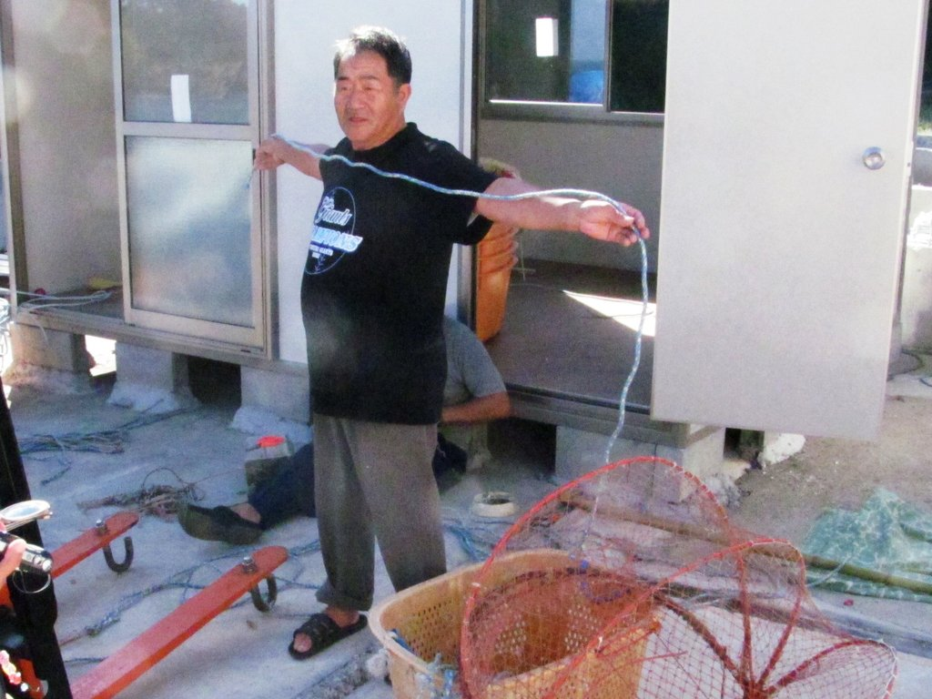 Yutaka Satoh shows octopus trap in front of shed