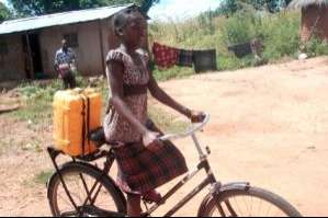 Priscah using her bike to help with chores