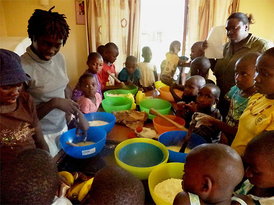 Children follow closely during a baking session