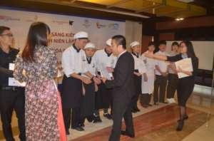 Cuong gets his diploma from the Hilton Hanoi GM