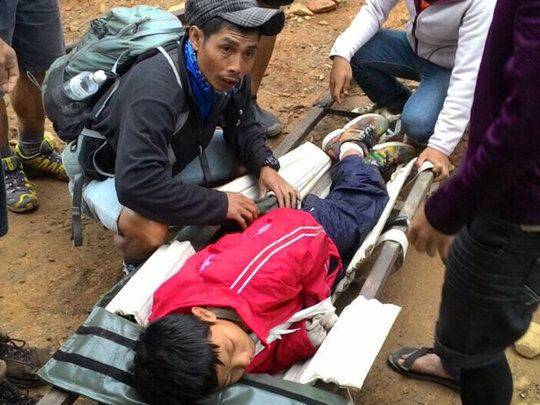Dusun mountain guides help a young injured climber