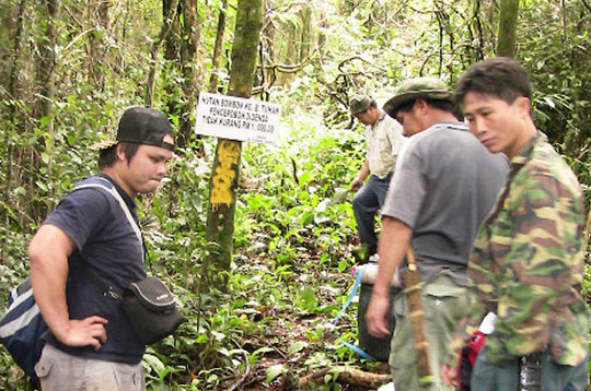 Taking GPS readings at forest border with leaders
