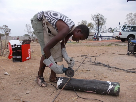 Charity wielding a grinder to cut round bar