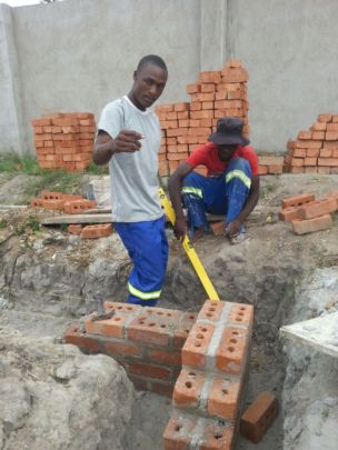 Foster instructing Nkosi on foundation building