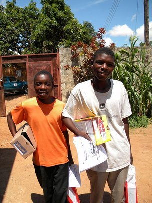 Samuel and Douglas receiving school supplies
