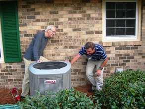 Co-op worker and homeowner inspect a new heat pump