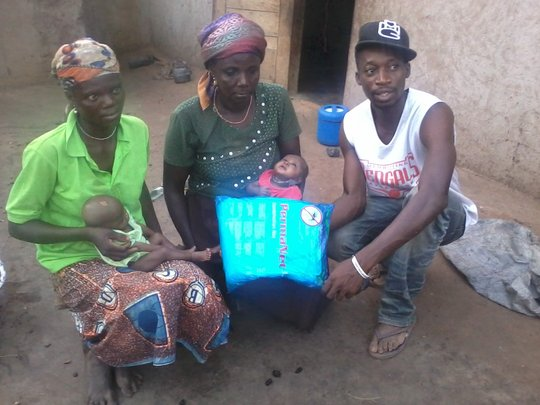 A mother with her twins receiving donated net