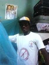 Malaria team member haning bed net in Cape Coast