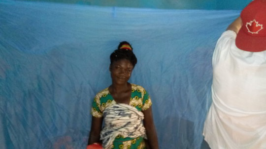 A beneficiary smiles after receiving bed net