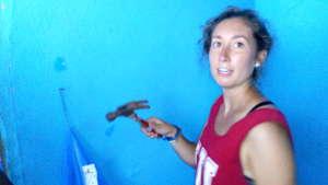 Hannah completes nailing the wall to hang a net.