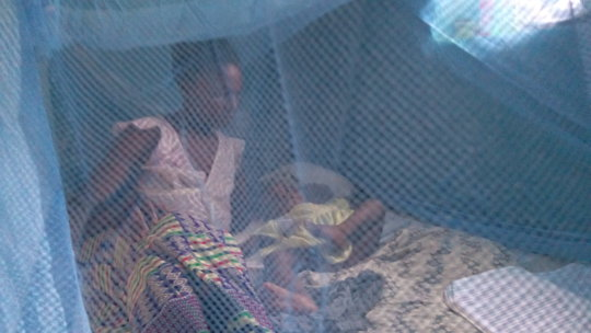 Beneficiary and baby under treated bed net.