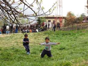 Two kids playing by the side of archery field.