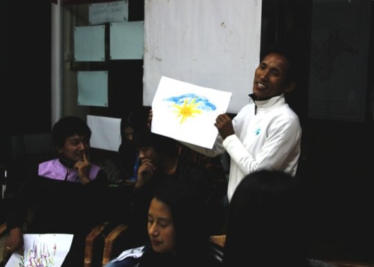 A participant shares his art with the rest
