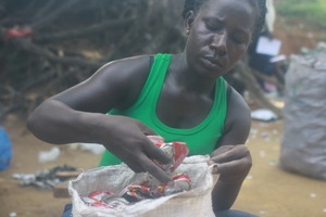 Worker Alice Sukuta gathers crushed cans.