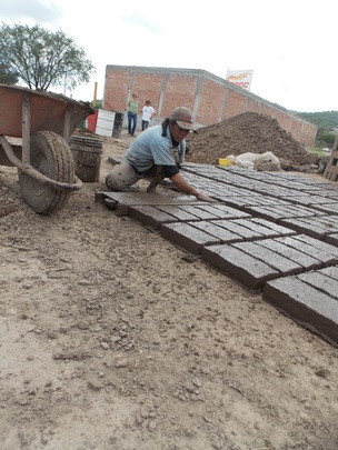 Maria making bricks by hand.