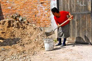 Juana gladly helps build Casita #47, her new home.