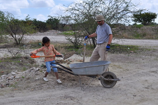 A family member shows a volunteer how it's done.