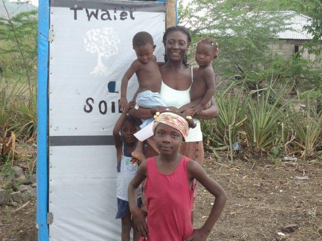 A family shows off their SOIL toilet