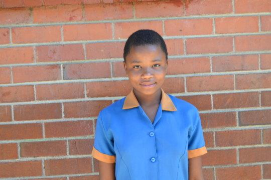 Audrey in a school uniform happy