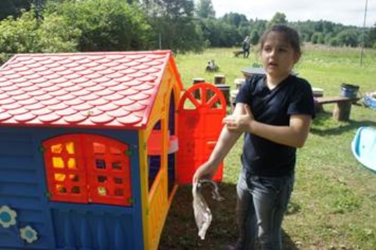 Ira cleaning the wendy house for the children